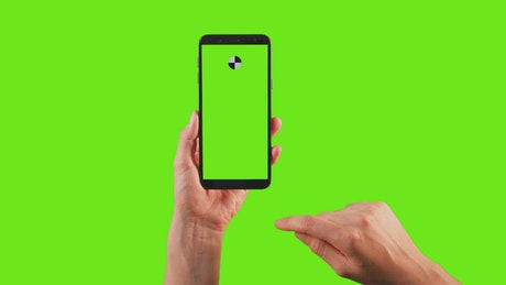 Hands using a cellphone with tracking point on a green background