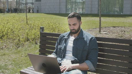 Handsome arab man sitting on park bench with laptop
