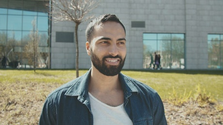Handsome Arab man smiles at camera outside building