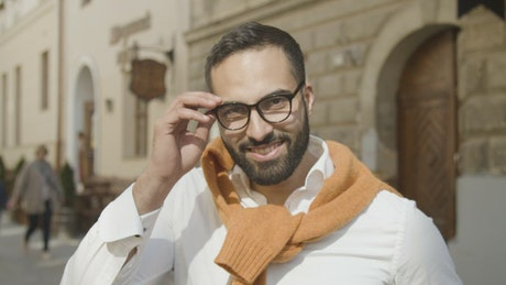 Handsome arab man takes off glasses and smiles