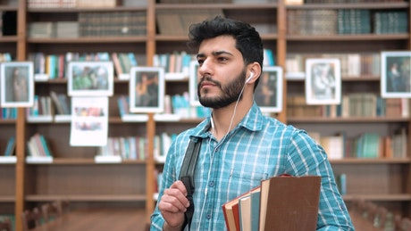 Handsome smiling university student with books