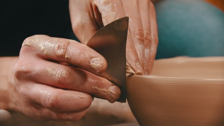 Hans molding a clay bowl with a metal tool