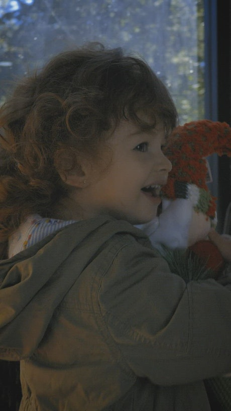 Happy and funny girl with a stuffed Santa Claus