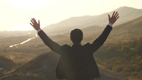 Happy businessman raises hands seen from behind