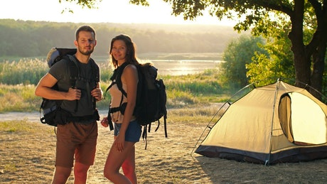 Happy camping couple watching together at camera