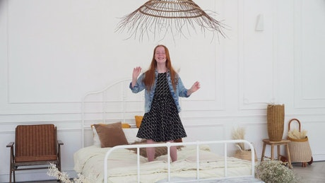 Happy child jumping on a bed