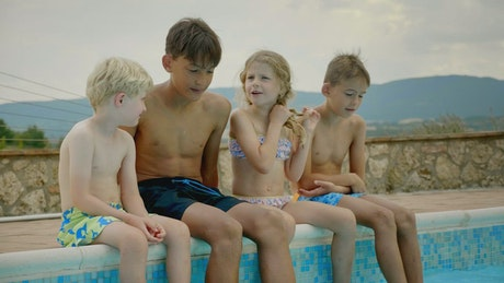 Happy children talking sitting on the edge of the pool