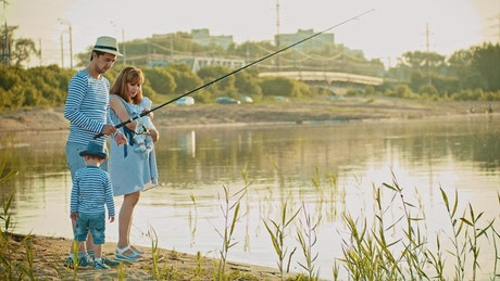 Happy family fishing on the shore of a lake