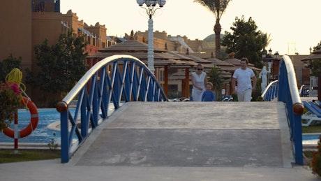 Happy family running across a bridge