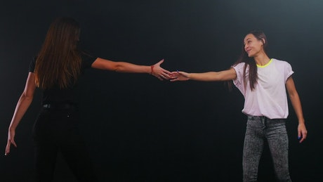 Happy female friends dancing on black background