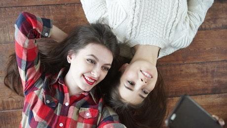 Happy female friends taking selfies on the floor