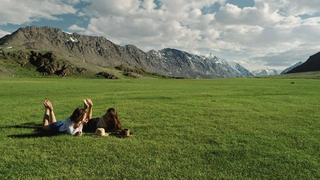 Happy female friends talking on nature