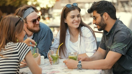 Happy friends chat while having drinks outdoors