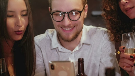 Happy friends looking at photo in a bar