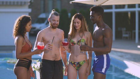 Happy friends toasting beside a swimming pool