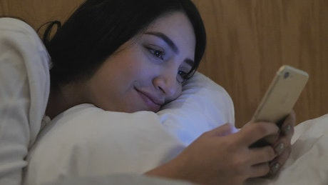Happy girl lying down sending messages at night