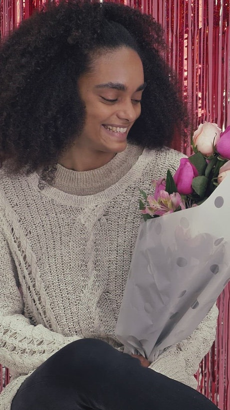 Happy girl smelling a bouquet of flowers on Valentine's Day