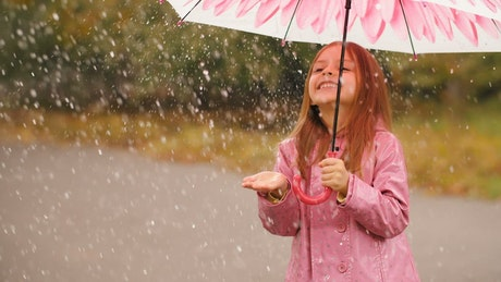 Happy girl with an umbrella in the rain