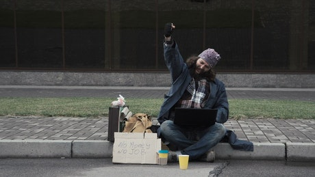 Happy homeless with laptop celebrating
