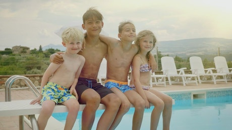 Happy kids sit on diving board of pool posing for photo