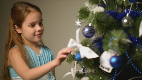 Happy little girl next to a Christmas tree