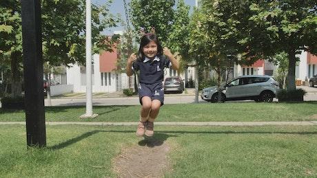 Happy little girl on a swing in a park