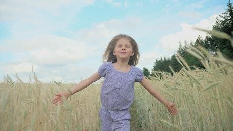 Happy little girl running through field
