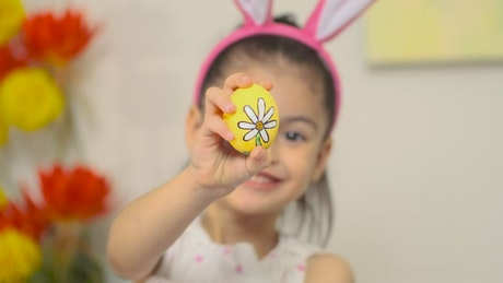 Happy little girl showing an easter egg