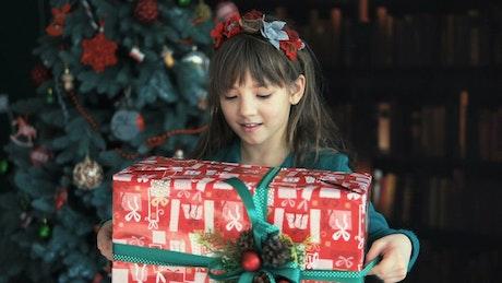 Happy little girl waving her Christmas gift