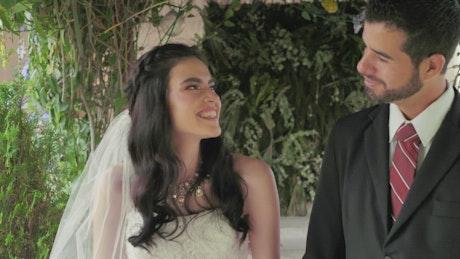 Happy newlywed couple walk hand in hand