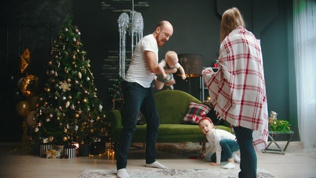 Happy parents play with their daughters at Christmas
