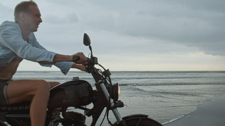 Happy wanderlust riding a motorcycle at the beach