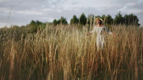 Happy woman in hat runs through tall grass