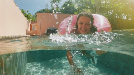 Happy woman in the swimming pool enjoying vacations