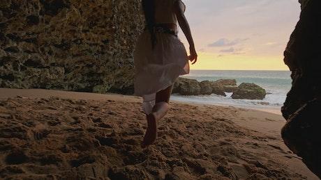 Happy woman in white dress runs to the sea