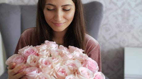 Happy woman smelling a bouquet of pink roses