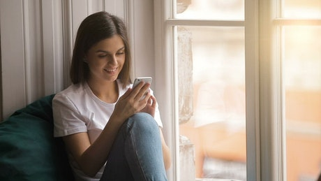 Happy woman uses mobile app sitting in window