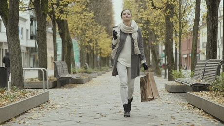 Happy woman walking with shopping bags at autumn