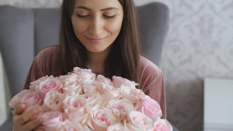 Happy woman with her bouquet of pink flowers