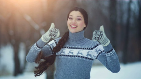 Happy woman with thumbs up in snowy forest