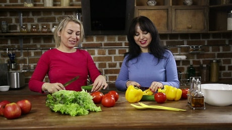 Happy women cutting vegetables at home