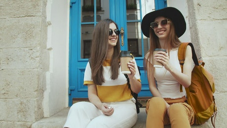 Happy women toast and drink coffee on steps