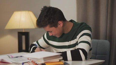 Happy young man writing with pen and paper
