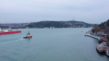 Harbour pilot boat following a cargo ship
