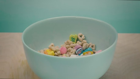 Healthy cereal in a bowl while pouring milk