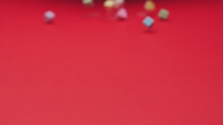Heart candies sliding on a red surface