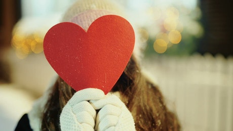 Heart cutout reveals smiling young woman in winter scene