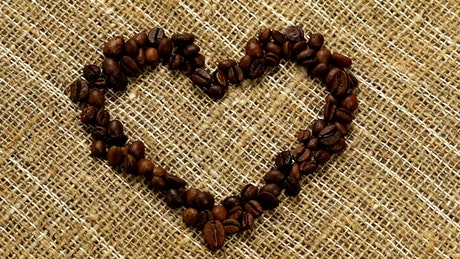 Heart of coffee filled with coffee beans on a sack