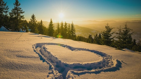 Heart shape in the snow mountains at sunset