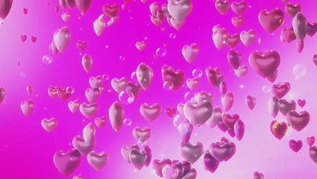 Heart-shaped balloons rising on pink background